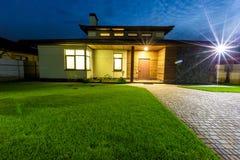Fristående lyxigt hus på den främre ingången för nattsikt utifrån Royaltyfria Bilder