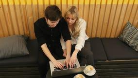 Fristående par genom att använda bärbar datordatoren i coffee shop Fotografering för Bildbyråer