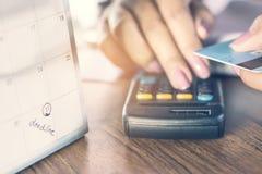 Fristenkalenderanmerkung mit Unschärfehintergrund der Geschäftsfrauhand, die ihre Schuld auf Taschenrechner mit der Hand hält Kre Stockbilder