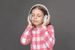 fristil Flicka i hörlurar som står isolerad på grå färger som lyssnar till närbilden för stängda ögon för musik den glade arkivfoton