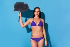 fristil Kvinna i bikinianseende som isoleras på den blåa väggen med den säkra anförandebubblan arkivfoto
