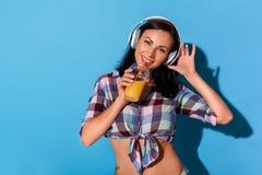 fristil Kvinna i hörlurar med kalt bukanseende som isoleras på den blåa väggen med att dricka smoothien som lyssnar till musik royaltyfri fotografi