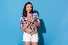 fristil Kvinna i kortslutningar med kalt bukanseende som isoleras på den blåa väggen genom att använda appen på att le för smartp arkivbilder