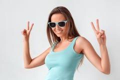 fristil Kvinna i solglasögon som står studion som isoleras på vitt visande le för fredtecken som är gladlynt royaltyfri fotografi