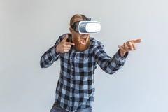 fristil Mogen man i virtuell verklighethörlurar med mikrofonanseende som isoleras på grå spela skytte med det imaginära vapnet royaltyfria foton
