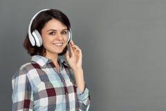 fristil Ung kvinna i hörlurar som isoleras på grå lyssnande musik som ler lycklig närbild fotografering för bildbyråer