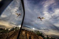 Fristilcyklisten hoppar med motorcykeln och reflekterar i spegel arkivbild