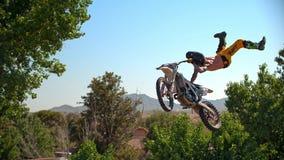 Fristilmotocrosscyklisten utf?r tricket i hopp p? fmxkonkurrenser arkivfoton