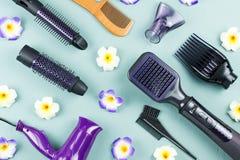 Frisurnwerkzeuge mit Blumen auf blauem hölzernem Hintergrund Stockfoto