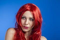 Frisyr attraktiv kvinna med enorm röd man, blå chroma royaltyfria bilder