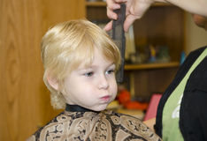 Frisyr av den unga blonda pojken i salong Fotografering för Bildbyråer
