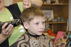 Frisyr av den unga brunettpojken i salong Fotografering för Bildbyråer