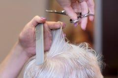 Frisyr för åldringen Processen av att klippa mormoderns hår i barberaren shoppar royaltyfria bilder