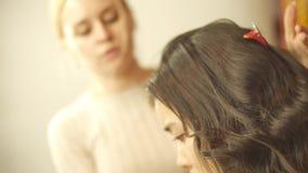 Frisyr händer för frisör` s som arbetar genom att använda hårspray på hår för klient` s på salongen den långa skinande krullninge arkivfilmer