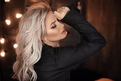 frisyr Härlig blond kvinnastående som poserar i svart skjorta Trendig blond flickamodell över mörk bakgrund för bokehljus arkivfoto