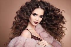 frisyr lockigt hår Modebrunettflicka med lång lockig hai royaltyfria bilder
