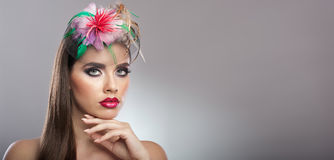 Frisyr och smink - härlig äkta naturlig brunett med kulöra blommor i hennes långa hår. Konststående Royaltyfri Foto