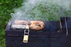 Frit chiken les morceaux sur le gril avec du bois brûlant Repas savoureux chaud de barbecue de smokey aux charbons et au bois de  photographie stock libre de droits