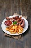 Frita a batata, os reforços de carne de porco e o molho de tomate fotografia de stock