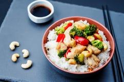 Fritada da agitação da galinha do caju dos brócolis da pimenta vermelha com arroz Fotografia de Stock