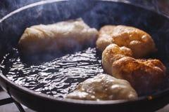 Fritada de los buñuelos en el sartén Imagen de archivo libre de regalías