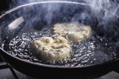 Fritada de los buñuelos en el sartén Foto de archivo