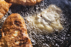 Fritada de los buñuelos en el sartén Fotos de archivo