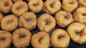 Fritada de los dulces en aceite caliente en confitería almacen de metraje de vídeo