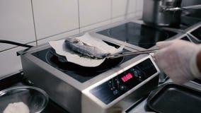 Fritada de pescado en el documento de pergamino sobre una parrilla de la cacerola metrajes