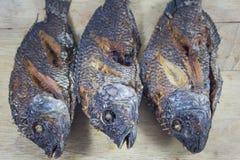 Fritada del cuerpo de tres pescados en la madera que taja Fotos de archivo libres de regalías