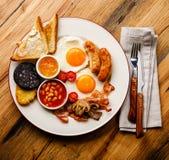 Fritada llena encima del desayuno inglés con los huevos fritos, salchichas, tocino foto de archivo