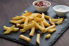 Fritadas de Fried French, molho de tomate e sal em um quadro-negro imagens de stock royalty free