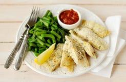 Fritadas de pescado cortezudas de la sémola del limón con las habas verdes y Marinara Foto de archivo