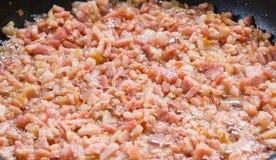 Fritando bocados do bacon na frigideira fotos de stock royalty free