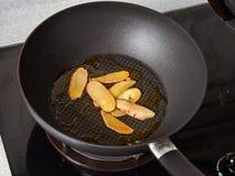 Fritando mexendo o gengibre no calor elevado para trazer adiante o aroma saboroso com óleo de sésamo imagens de stock