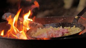Fritando o bacon e as batatas sobre a fogueira video estoque