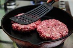 Fritando o hamburguer cru Imagem de Stock Royalty Free