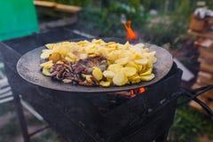 Frite batatas no fogo aberto no ar livre fotografia de stock royalty free