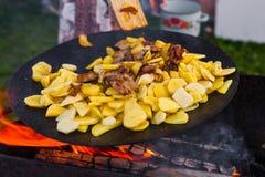 Frite batatas no fogo aberto no ar livre fotografia de stock
