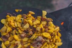 Frite batatas no fogo aberto no ar livre imagem de stock royalty free