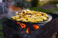 Frite batatas no fogo aberto no ar livre imagens de stock royalty free
