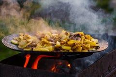 Frite batatas no fogo aberto no ar livre fotos de stock