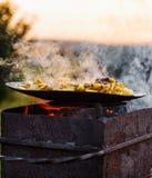 Frite batatas no fogo aberto no ar livre imagens de stock