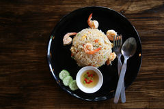 Frite o arroz com o camarão no prato preto na tabela do marrom escuro, colher, para fotografia de stock