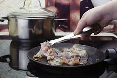 Frite o bacon na frigideira, a m?o da menina p?e o bacon na frigideira, cozinhando na cozinha sobre o fog?o cer?mico imagens de stock royalty free