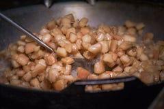 Frite a pele da carne de porco em uma grande frigideira no fogão imagem de stock