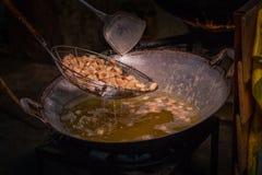 Frite a pele da carne de porco em uma grande frigideira no fogão imagens de stock