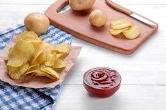 Frites, casse-croûte et sauce rouge sur une table en bois blanche Nourriture malsaine photo stock