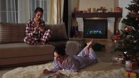 Fritid av två tvilling- systrar i pyjamas Härliga flickor, i att sova dräkter En flicka skrivar ut på en cell, medan sitta på a lager videofilmer