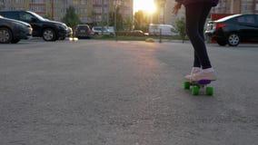 Fritidsaktivitet för sikt för stad för flickaskateboardsolnedgång stock video